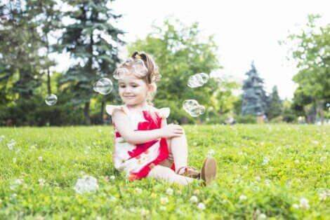 Little girl sitting in the grass to illustrate having chidren at a family picnic