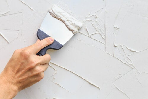 A person repairing their walls.