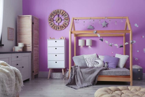 A bedroom with a purple wall.