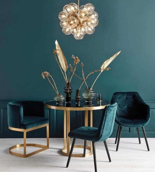 A dining room with some gold accents.