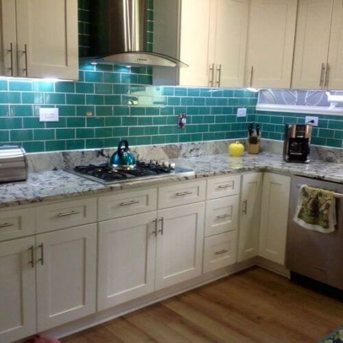 A kitchen with some emerald blue tiles.