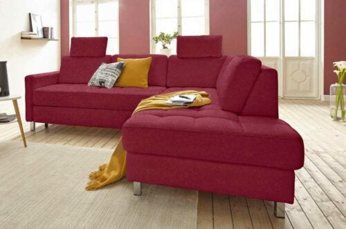A maroon sofa with some pillows and a throw.