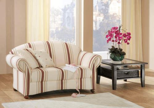 A small striped sofa beside a table with flowers.