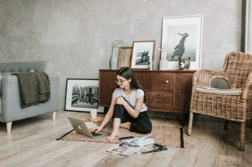 A woman sitting on the floor of her city apartment.