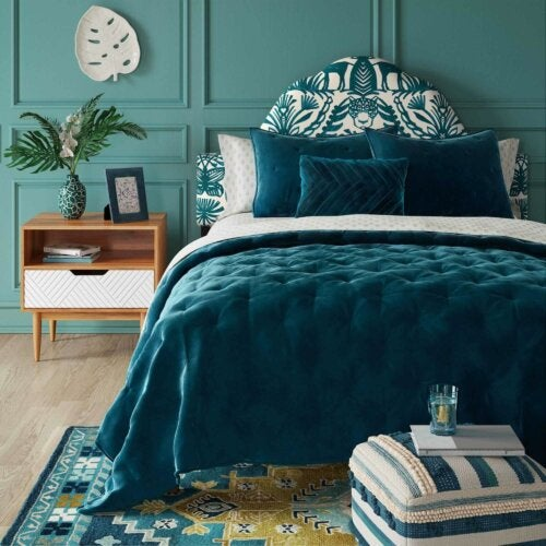 An emerald blue bed in a bedroom.