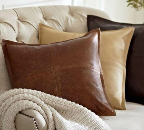 Some faux leather pillows on a sofa.