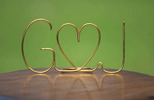 The initials of two people in gold wire.