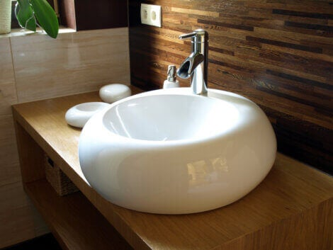 A white round sink on a brown vanity to update your bathroom.
