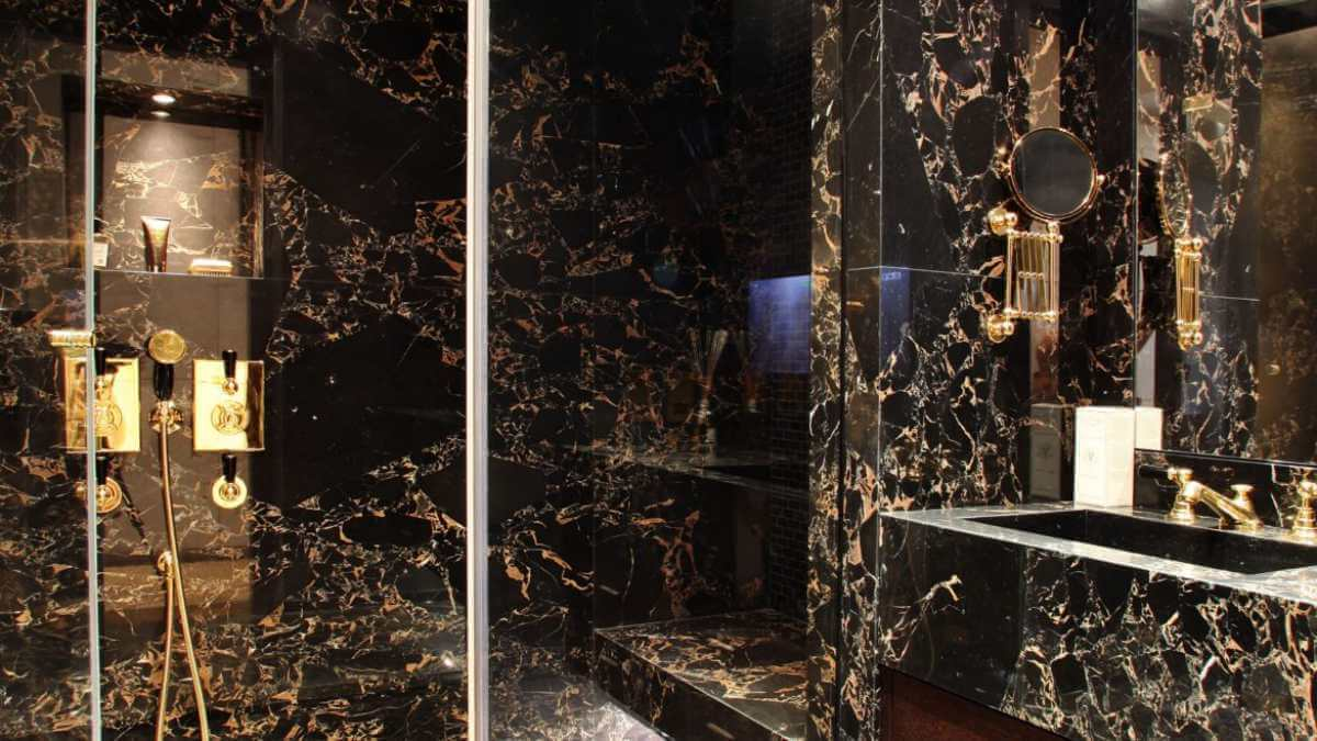 A dark restroom with gold decor
