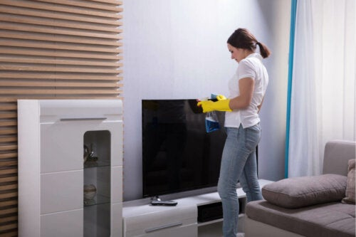 A woman cleaning a TV screen.