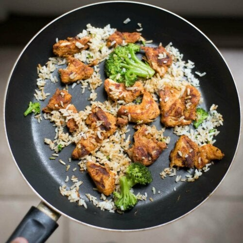 A pan with some chicken, rice and broccoli.