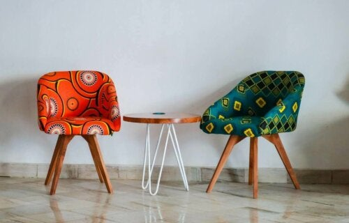 Some multicolored upholstered armchairs by a table.