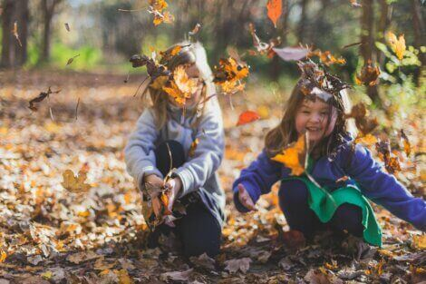 Children gathering up leaves in a yard