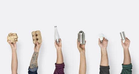 Four hands holding up recyclable items for a sustainable house