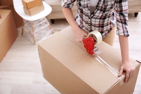 A person taping up a cardboard box, organization to show distadning