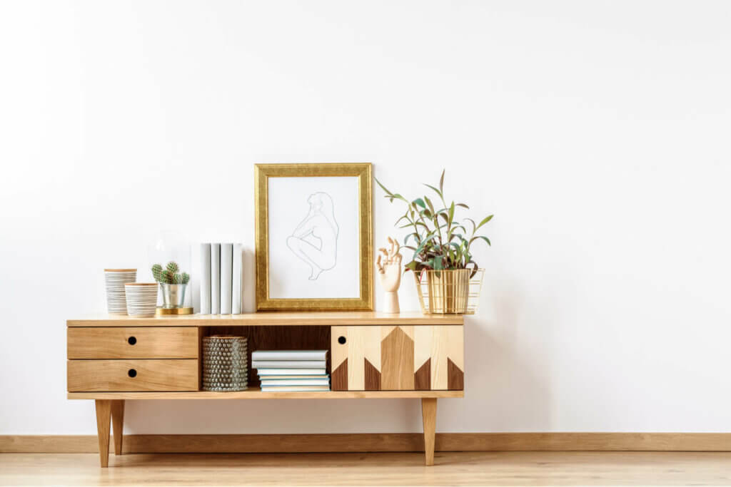 A wood sideboard with mirror.