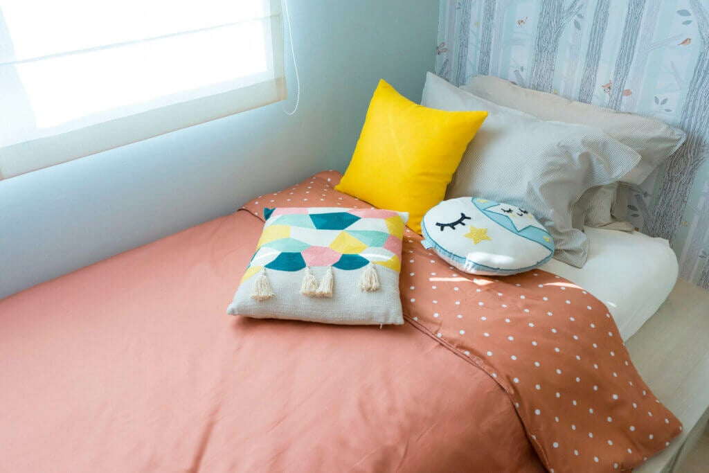 A child's bed with pink and yellow bedclothes.
