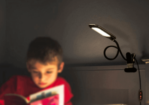 A boy reading a book under the light of his flexible lamp.
