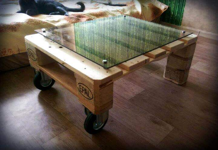 Table made of wooden pallets, with glass pane on top.
